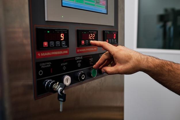 Trabalhador em uma fábrica, pressione o botão de uma máquina