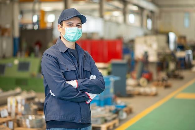 Trabalhador em uma fábrica usando uma máscara durante a pandemia de coronavírus covid-19