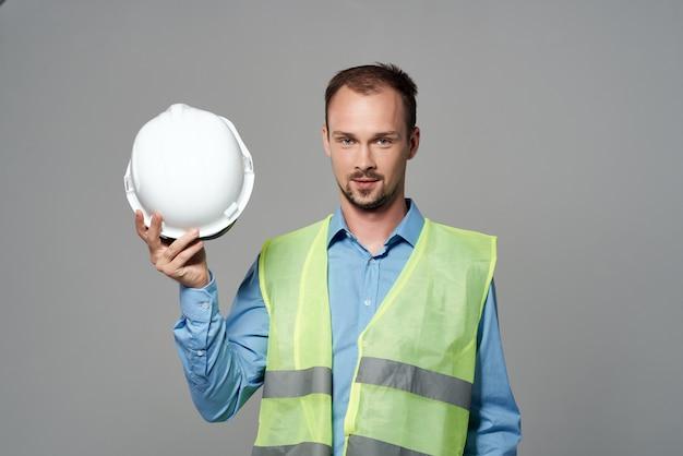 Trabalhador em uma luz de fundo de segurança de engenheiro de capacete branco