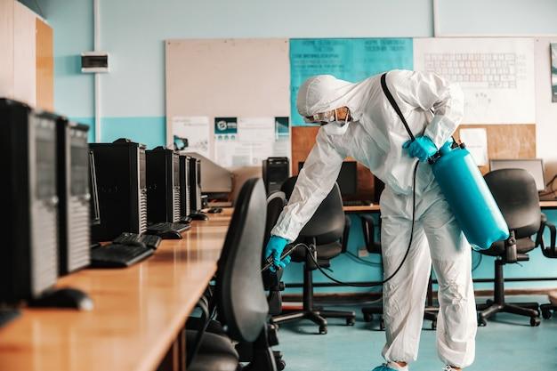 Trabalhador em uniforme branco estéril, com luvas de borracha e máscara segurando pulverizador com desinfetante e gabinete de esterilização de informática na escola.