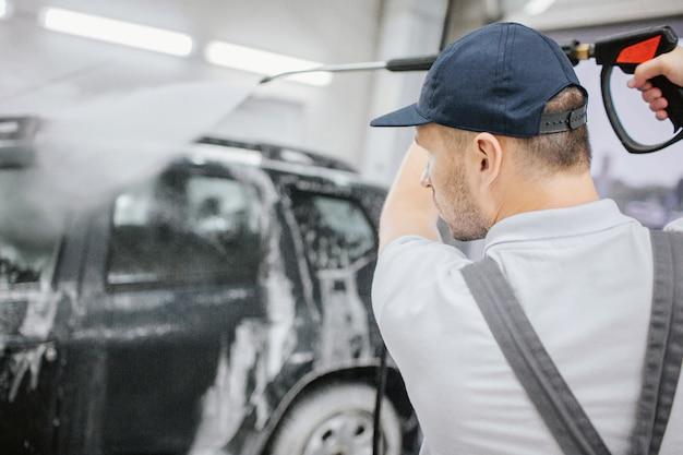 Trabalhador em uniforme cinza fica no carro preto coberto com espuma. ele segura uma mangueira flexível com pistola e lava automóveis. o homem é sério e concentrado. ele está na garagem.