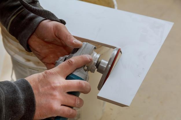 Trabalhador em usa moedor para cortar azulejos de grés de porcelana