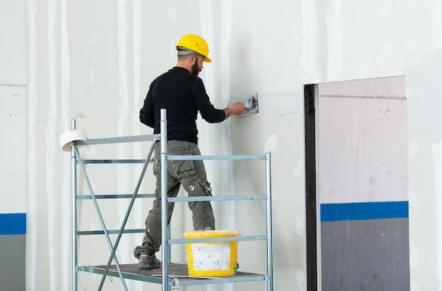 Trabalhador emplastrando a parede da placa de gipsita.