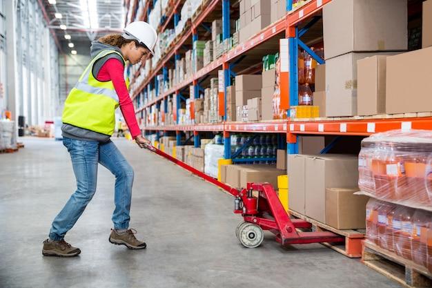 Trabalhador, empurrando o carrinho com caixas