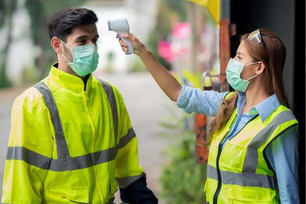 Trabalhador engenheiro máscara cirúrgica verificando a temperatura corporal usando termômetro digital infravermelho, verificar a temperatura antes de ir para o local de trabalho, trabalhadores com máscara protetora