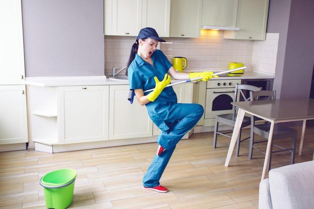 Trabalhador engraçado dançando na cozinha. ela finge tocar violão
