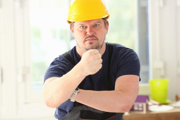 Trabalhador engraçado sorridente no levantamento de capacete amarelo