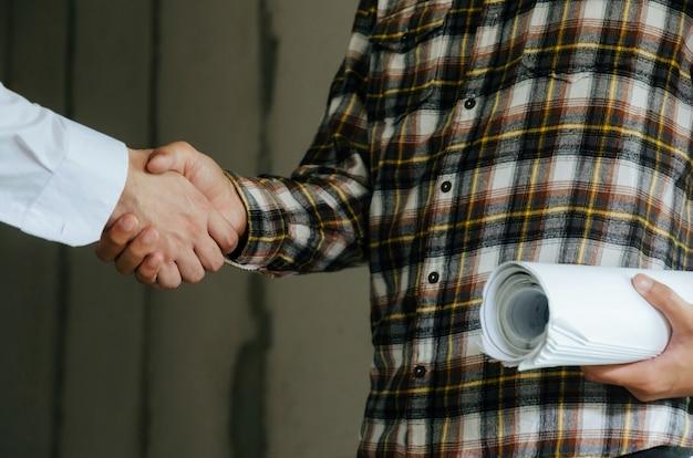 Trabalhador equipe contratante aperto de mão com engenheiro depois de conhecer o contrato de projeto no canteiro de obras