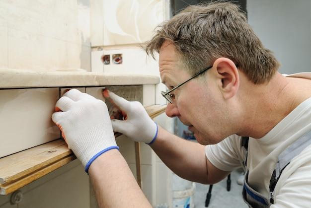 Trabalhador está colocando o pedaço de azulejo