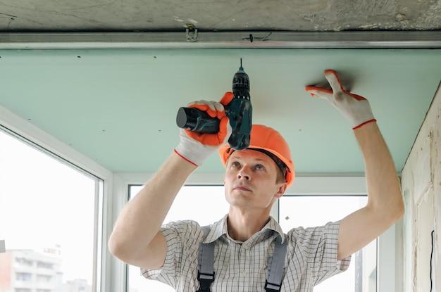 Trabalhador está consertando o drywall.