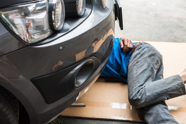Trabalhador está embaixo do carro para trocar o óleo do motor