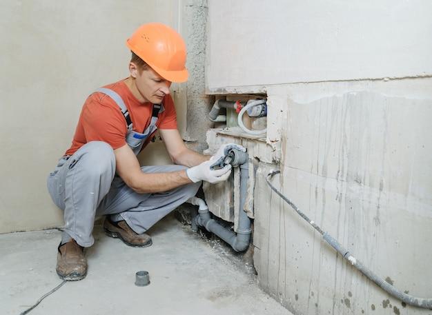 Trabalhador está instalando canos de esgoto