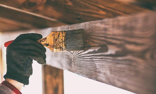 Trabalhador está pintando terraço de madeira