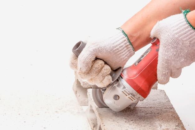 Trabalhador está usando rebarbadora para corte de bloco de cimento, ferramenta de mão, foco na lâmina