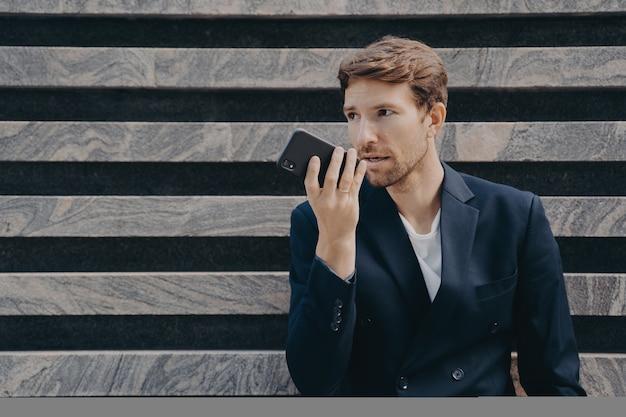 Trabalhador executivo do sexo masculino vestido formalmente segurando smartphone perto de falar com a boca no viva-voz