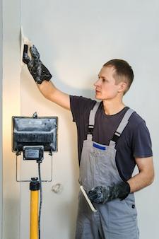 Trabalhador faz final de alisamento de gesso na parede.