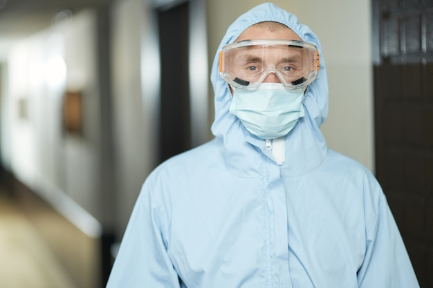 Trabalhador fazendo higienização enquanto usava roupa anti-perigosa
