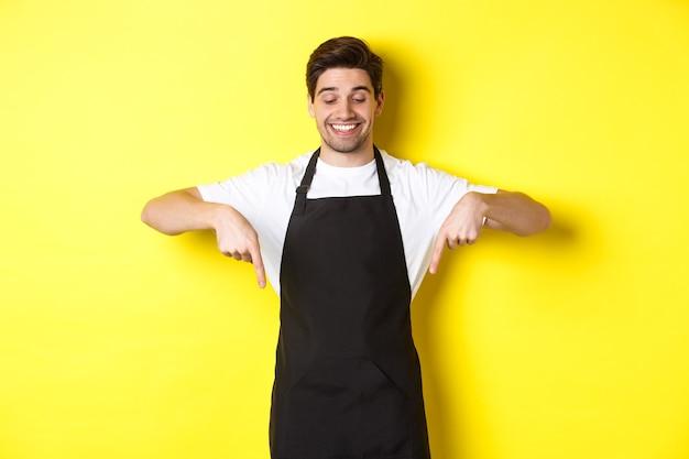 Trabalhador feliz da cafeteria com avental preto apontando os dedos para baixo, parecendo satisfeito e sorrindo, mostrando o logotipo, em pé sobre a parede amarela