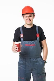 Trabalhador feliz no capacete, segurando o copo de papel com café para ir e sorrindo para a câmera