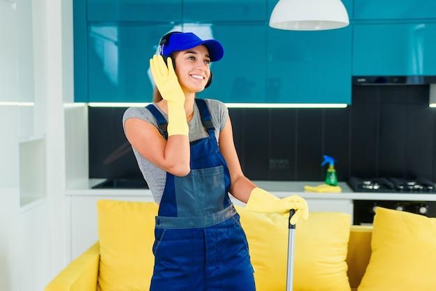 Trabalhador feminino atraente com fones de ouvido dançando com o swabber no meio da cozinha contemporânea