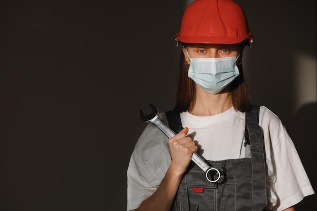 Trabalhador feminino retrato é usar máscara de proteção facial, capacete de segurança e terno e com uma grande chave de parafuso, chave inglesa nas mãos.