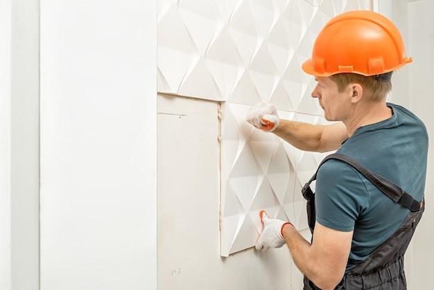Trabalhador fixando o painel 3d de gesso na parede