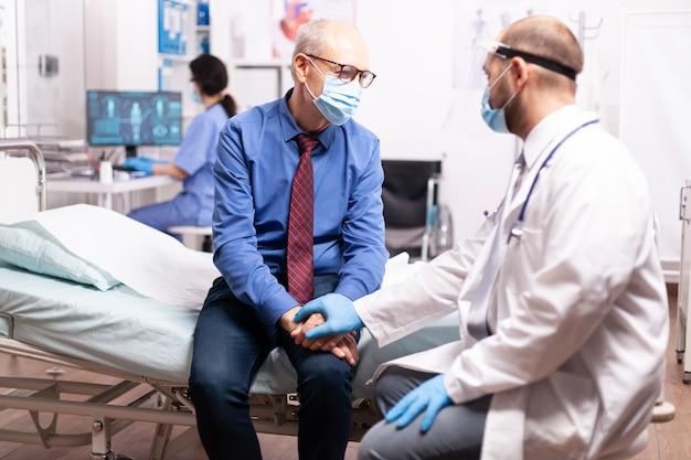 Trabalhador giátrico oferecendo compaixão a um homem idoso em clínica particular