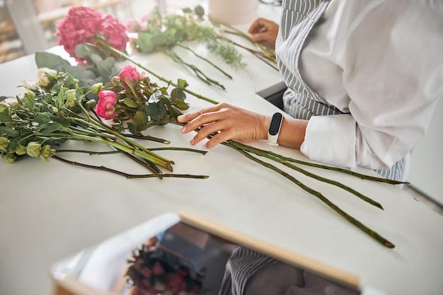 Trabalhador habilidoso da floricultura tocando flores na mesa