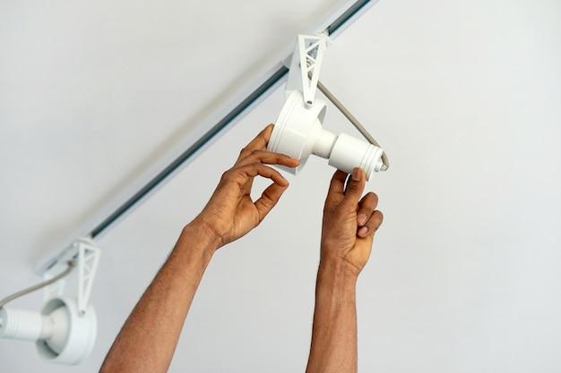 Trabalhador homem eletricista africano instalar um teto led holofotes