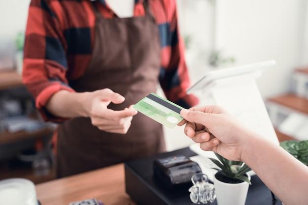 Trabalhador homem no balcão de café, recebendo pagamento