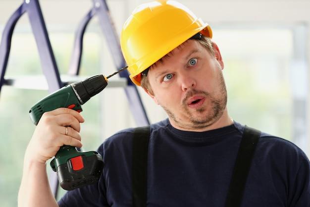Trabalhador idiota usando furadeira elétrica