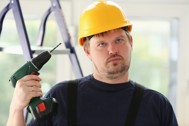 Trabalhador idiota usando retrato de furadeira elétrica