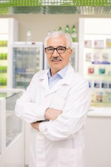Trabalhador idoso de drogaria com jaleco branco e óculos cruzando os braços sobre o peito enquanto fica de pé junto ao local de trabalho em frente a vitrines com itens médicos