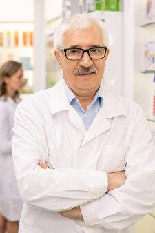 Trabalhador idoso de drogaria de jaleco branco e óculos, cruzando os braços sobre o peito, em pé contra vitrines com produtos médicos e seu colega