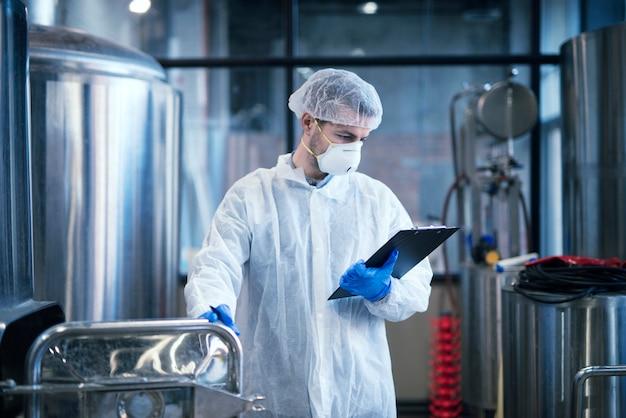 Trabalhador industrial com roupas protetoras brancas segurando uma lista de verificação e lendo os resultados
