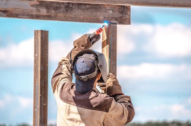 Trabalhador industrial cortando metal ao ar livre