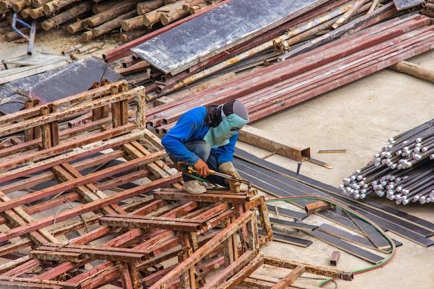 Trabalhador industrial da soldadura para a construção do trabalho de aço na construção da área com processo de soldadura.