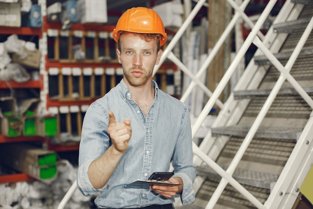 Trabalhador industrial dentro de casa na fábrica. empresário com capacete laranja. homem de camisa azul.