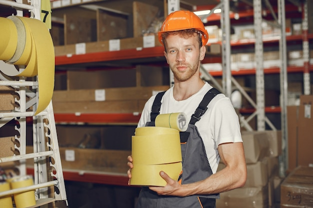 Trabalhador industrial dentro de casa na fábrica. jovem técnico com capacete laranja.