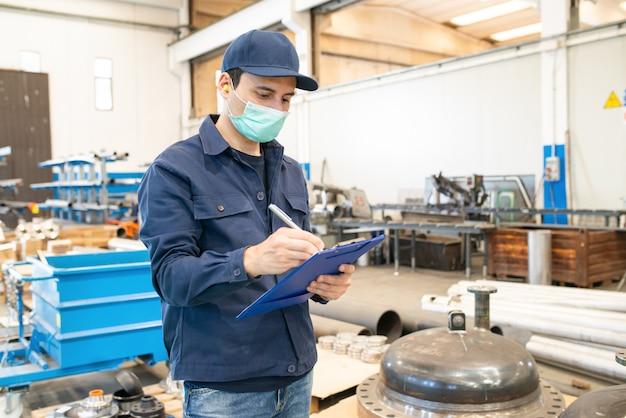 Trabalhador industrial, escrevendo em um documento em uma fábrica