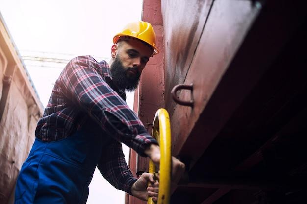 Trabalhador industrial girando a roda e fechando a válvula no vagão do trem.
