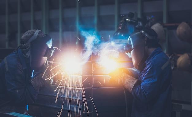 Trabalhador industrial na estrutura de aço de solda de fábrica