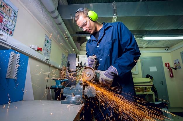 Trabalhador industrial pesado na fábrica de metal com a ferramenta de moagem elétrica