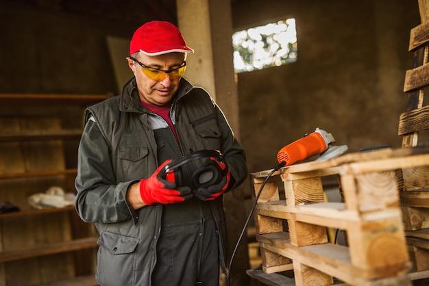 Trabalhador industrial profissional moderno de uniforme, colocando a proteção para os ouvidos em pé perto de paletes de madeira e o moedor elétrico.