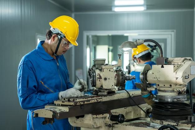 Trabalhador industrial trabalhando na fábrica, fábrica de fabricação industrial de torno de metal.