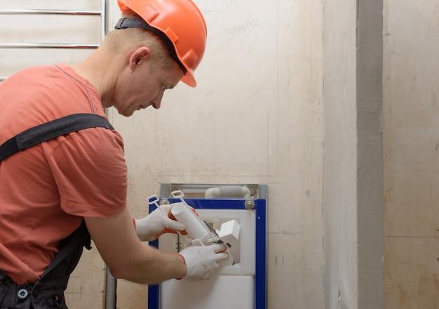 Trabalhador, inserindo a válvula de descarga do vaso sanitário no tanque embutido