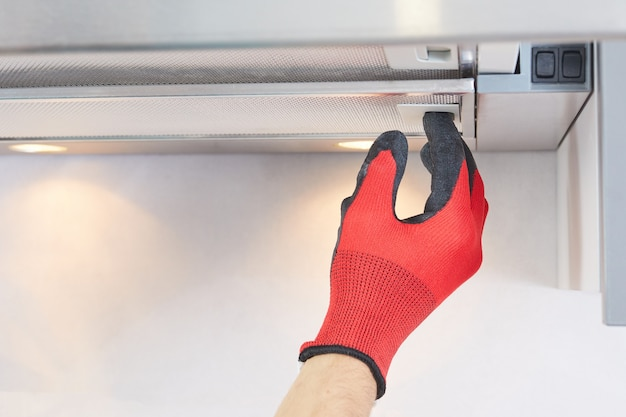 Trabalhador instala o filtro no exaustor da cozinha. faz-tudo removendo o filtro de um exaustor. reparação do exaustor.