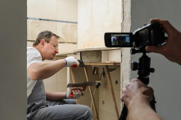 Trabalhador instala telhas cerâmicas. o operador está filmando esse processo.