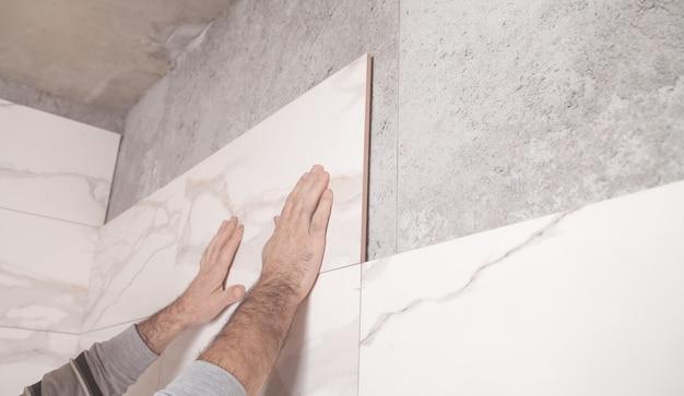 Trabalhador instalando azulejo na parede