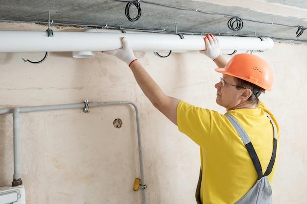 Trabalhador instalando um sistema de ventilação no apartamento